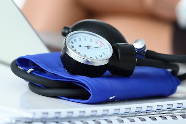 Крупным планом вид манометра, лежащего на рабочем столе в офисе врача. концепция здравоохранения, медицинского обслуживания, лечения, гипотонии или гипертонии.