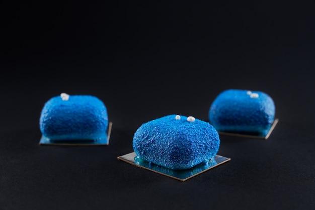 Крупным планом вид матового синего десерта, украшенного изолированными белыми шарами