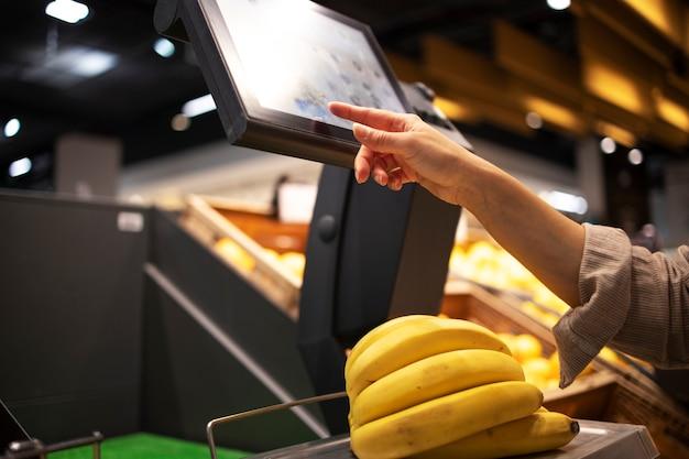 スーパーマーケットで果物の重量を測定するクローズアップビュー