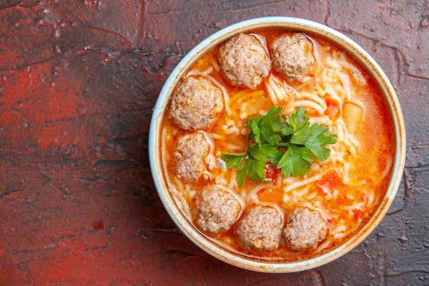 暗い背景の左側にある茶色のボウルに麺とミートボールのスープの拡大図