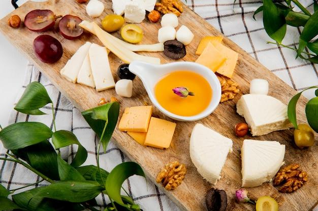 葉で飾られた格子縞のまな板の上のチーズグレープピースオリーブナッツの種類と溶けたバターのクローズアップビュー