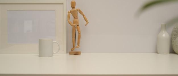 흰색 책상에 복사 공간, 프레임, 나무 그림, 화병 및 머그잔과 최소한의 홈 인테리어 디자인의 뷰를 닫습니다