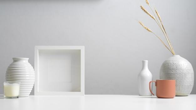 복사 공간이있는 최소한의 홈 인테리어 디자인의 뷰를 닫고 흰색 개념의 프레임, 꽃병 및 장식을 모의합니다.