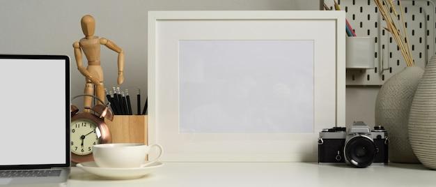 모의 프레임, 커피 컵, 노트북 및 사무용품이있는 최소한의 사무실 공간의 근접 촬영보기