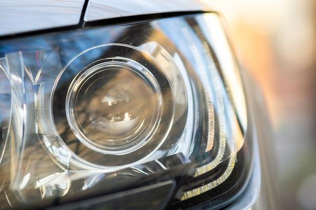 光沢のある光学系を持つ現代の車のヘッドライトのビューを閉じます。