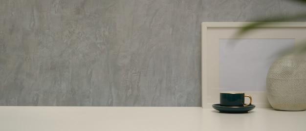 ロフトの壁が付いている机の上のコピースペース、モックアップフレーム、花瓶、カップとモダンなホームインテリアデザインのビューをクローズアップ