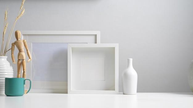 복사 공간이있는 현대 홈 인테리어 디자인의 뷰를 닫고 흰색 개념의 프레임, 꽃병 및 장식을 모의합니다.