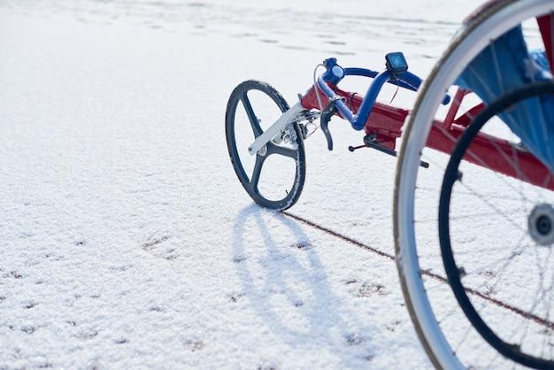 Крупным планом современная гоночная инвалидная коляска, стоящая на открытом воздухе на трассе, покрытой снегом