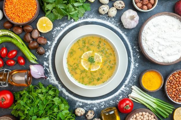 白いボウルにレモンとグリーンを添えた食欲をそそるスープの拡大図と小麦粉トマトオイルボトル小麦粉グリーンは暗闇の中で卵を束ねます
