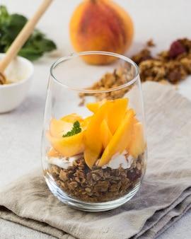 Крупным планом вид мюсли с персиками в стекле