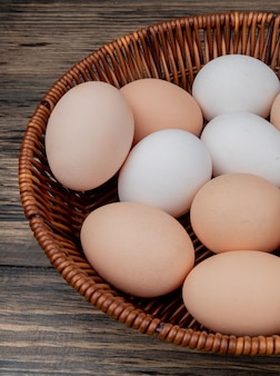 木製の背景にバケツに複数の卵のクローズアップ表示
