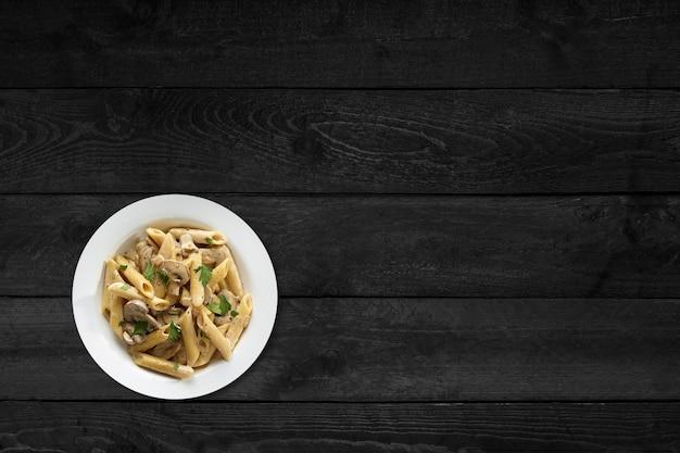 Крупным планом вид грибных макарон, изолированных на черном деревянном столе.