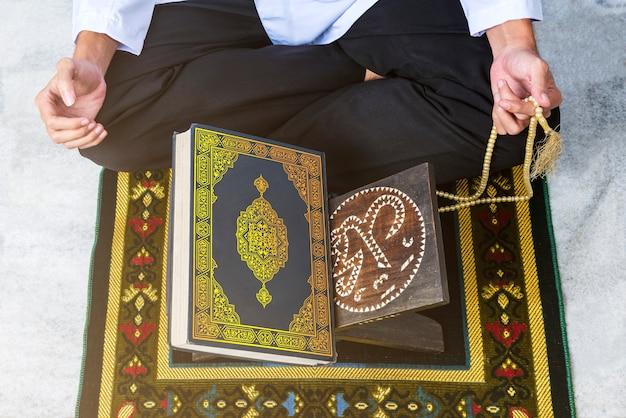 座っていると数珠で祈るイスラム教徒の男性のクローズアップ表示