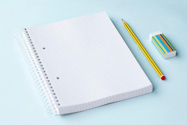 Крупным планом вид блокнота карандаша и ластика на голубом фоне