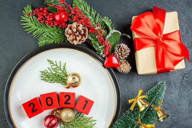 プレート上の数字の装飾アクセサリーのクローズアップモミの枝暗い背景の針葉樹の円錐形のクリスマスツリー