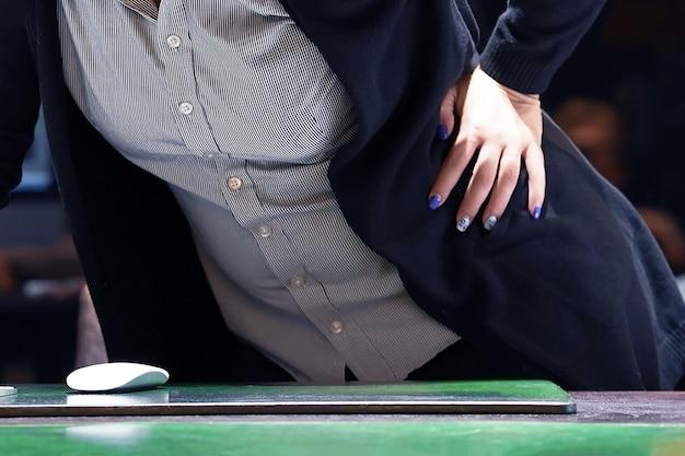 Взгляд конца-вверх женщины работника офиса с болью в почках. женщина с боли в спине, сжимая ее руку к ее нижней части спины.