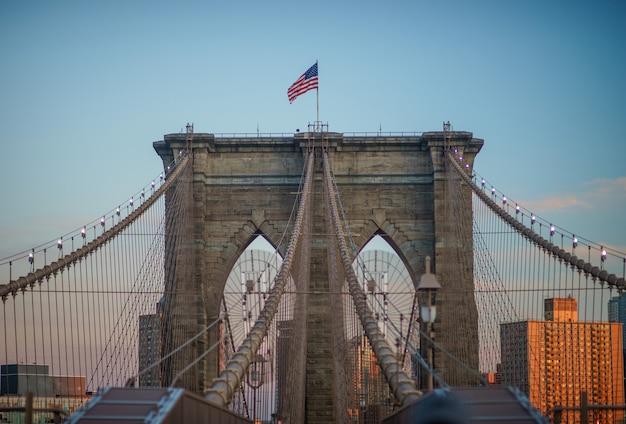 브루클린 다리의 타워 구조 중 하나의 뷰를 닫고 상단에 성조기 비행