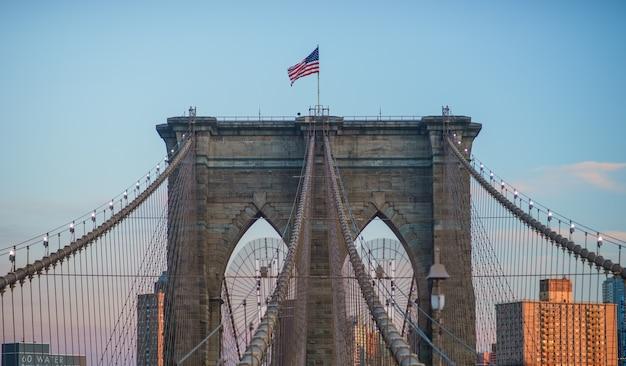 Крупным планом вид на одну из башен бруклинского моста, на вершине которой летят звезды и полосы.