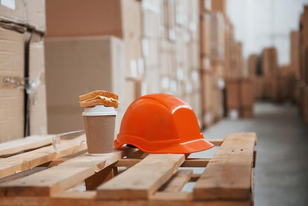 Крупным планом вид оранжевой каски, чашки напитка и бутерброда на складе.
