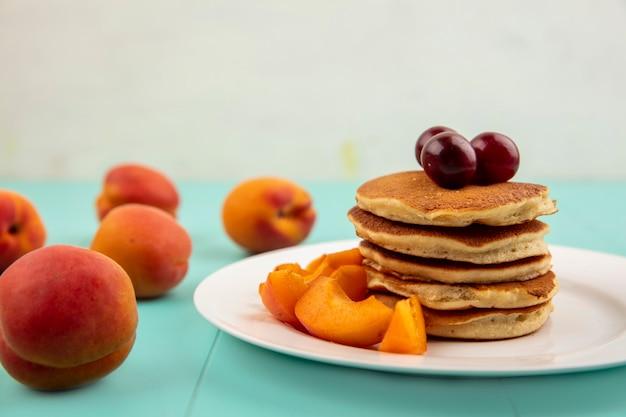 Крупным планом блины с кусочками абрикоса и вишней в тарелке и абрикосами на синей поверхности и белом фоне