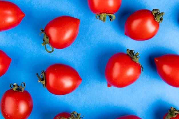 Взгляд конца-вверх картины томатов на голубой поверхности