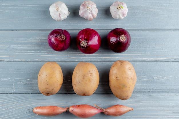 Закройте вверх по взгляду картины овощей как лук-шалот картошки лука чеснока на деревянной предпосылке с космосом экземпляра