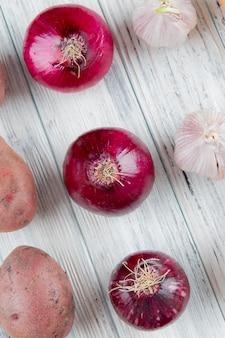 Закройте вверх по взгляду картины овощей как чеснок картошки красного лука на деревянной предпосылке