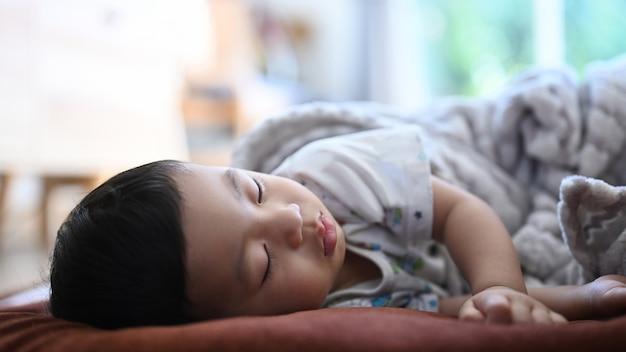 Крупным планом вид мирного ребенка, спящего на кровати в светлой комнате.