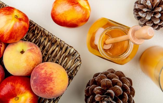Крупным планом вид персиков и стеклянной банке сливового варенья и сока с шишками на белом столе