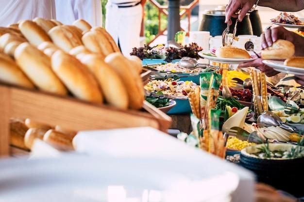 Крупным планом вид людей, руки друга берут еду со стола общественного питания во время празднования вечеринки