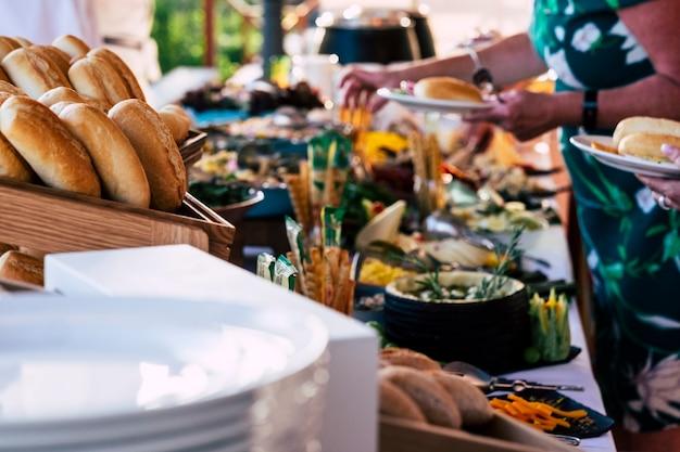 Крупным планом вид людей друзей руки берут еду со стола общественного питания во время празднования вечеринки