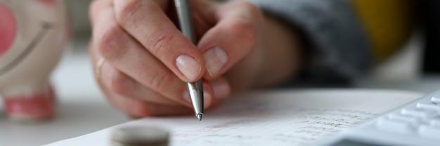 銀のペンを持っている人の手のクローズアップビュー。財務レポート付きのノートブック。デスクトップ上のコインの貯金箱。