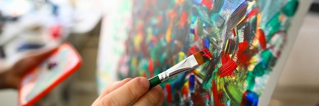 赤い色の絵筆を使用してキャンバスにペイントしている人の手のクローズアップビュー。抽象的なアートワーク。傑作の断片。創造的な趣味とアートのコンセプト