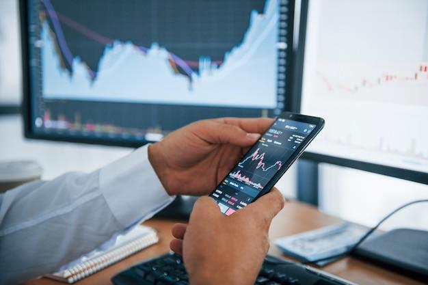Крупным планом зрения телефон держит руками человека. бизнесмен находится в офисе с несколькими экранами. понятие обмена и денег.
