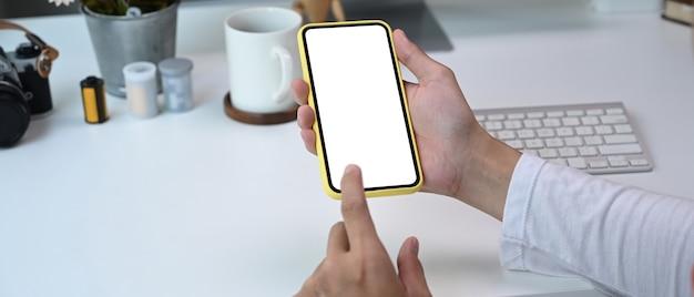 彼のオフィスの部屋で空白の画面で携帯電話を使用して写真家の手のビューをクローズアップ