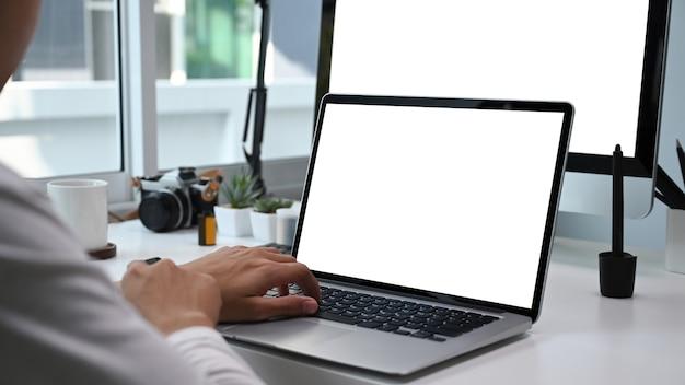 여러 장치로 작업하는 사진 작가 또는 그래픽 디자이너의보기를 닫습니다. 그래픽 디스플레이 몽타주를위한 빈 화면.