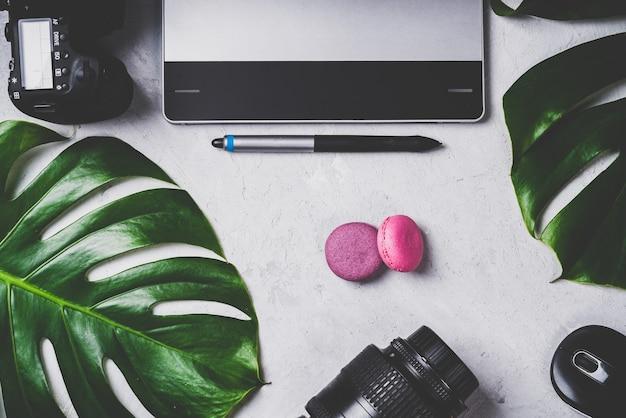 Крупным планом вид фотографа на рабочем месте графического дизайнера. планшет, стилус, фотоаппарат и зум-объектив, оптическая беспроводная мышь, макароны, зеленый лист монстера.