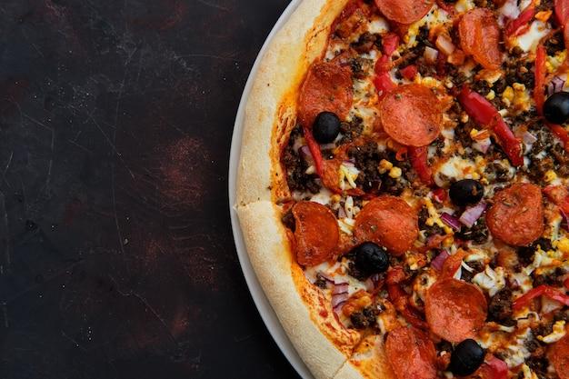 Крупным планом вид пиццы с фаршем, колбаса, перец, лук и оливки