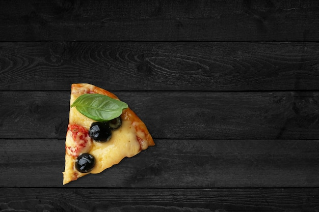 Крупным планом вид пиццы с плавленым сыром, изолированные на черном деревянном столе.