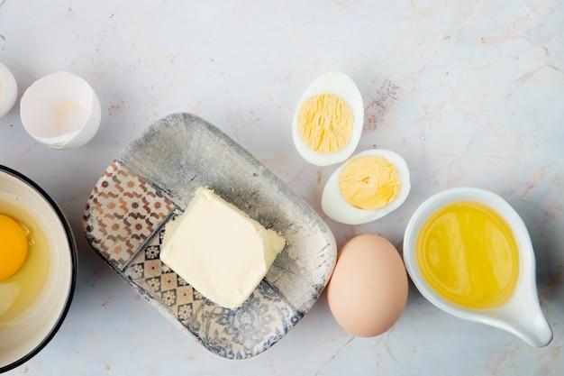 Взгляд конца-вверх плиты масла и яичек с топленым маслом и яичной скорлупы на белой предпосылке с космосом экземпляра
