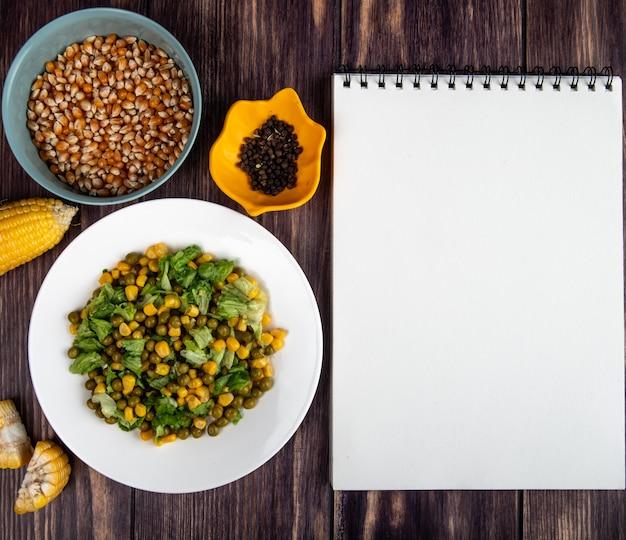 コピースペースを持つ木製の表面にトウモロコシの種子と黒コショウの種子とメモ帳とコーンサラダのプレートのクローズアップビュー