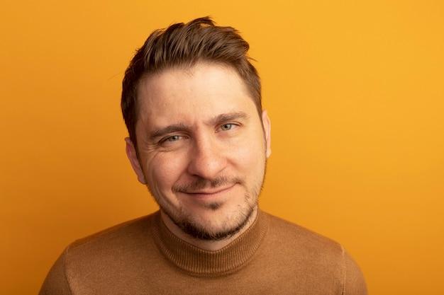 オレンジ色の壁に孤立して見える満足している若い金髪ハンサムな男の拡大図
