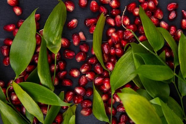 Крупным планом вид гранатовых ягод и листьев на черной поверхности