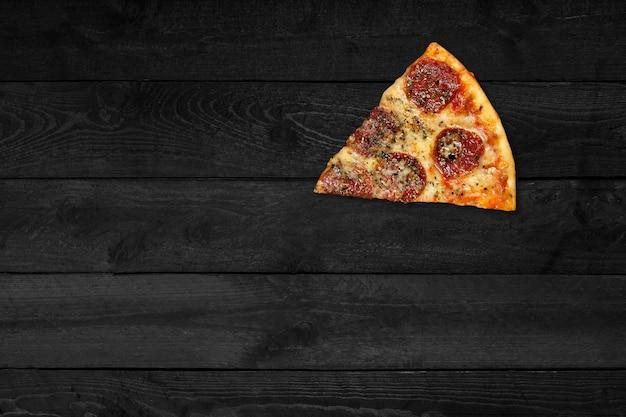 Крупным планом вид пиццы со свининой, изолированной на черном деревянном столе.