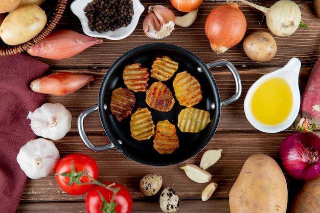 Крупным планом вид картофельных чипсов и овощей вокруг как чеснок лук помидор с черным перцем и маслом на деревянных фоне