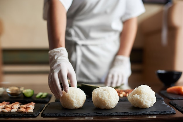 レストランで巻き寿司を調理するプロセスの拡大図。シェフがロールパンの材料を準備しています