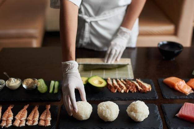 レストランで巻き寿司を調理するプロセスのクローズ アップ ビュー。シェフがロールの食材を準備しています