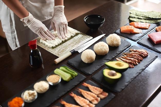 巻き寿司の作り方をクローズアップ。海苔と白ご飯。シェフの手がご飯に触れます。シェフが寿司を作り始める