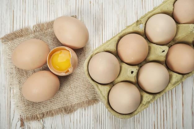 Крупным планом вид сырых куриных яиц в яичной коробке на деревянных фоне. сырые куриные яйца в яичной коробке органические продукты для хорошего здоровья с высоким содержанием белка.