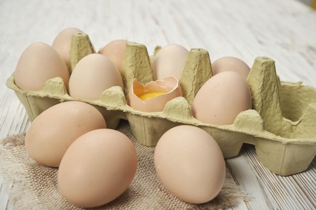 木製の背景の卵ボックスに生の鶏卵の拡大図。健康的な高タンパクのための卵ボックス有機食品の生鶏卵。
